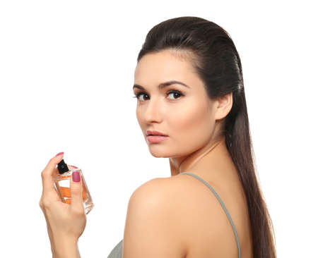 Beautiful young woman with bottle of perfume on white background