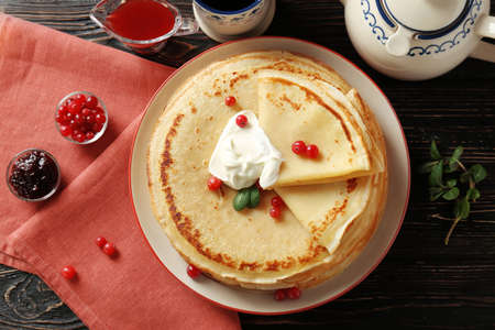 Tasty pancakes with cream and berries on table
