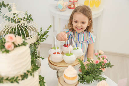 Cute girl taking sweets served for party
