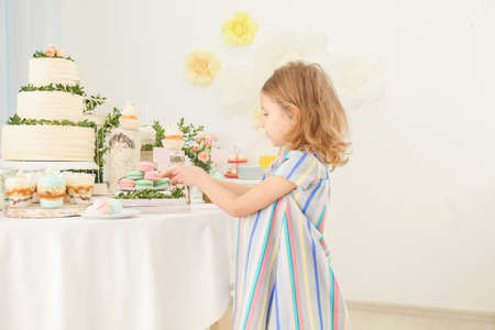 Cute girl near table with sweets served for party