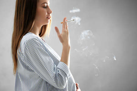 Pregnant woman smoking cigarette on grey background