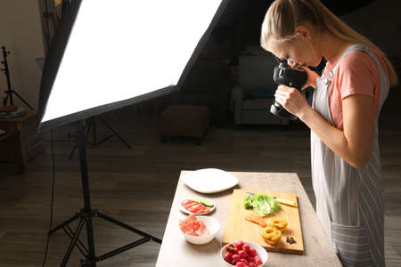 Young woman photographing food in photo studio