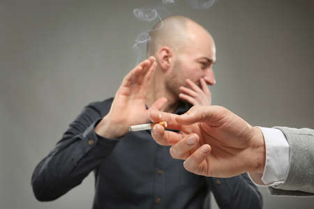 Young man refusing from smoking on grey background