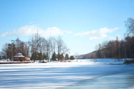 Beautiful winter landscape with frozen river and blue sky