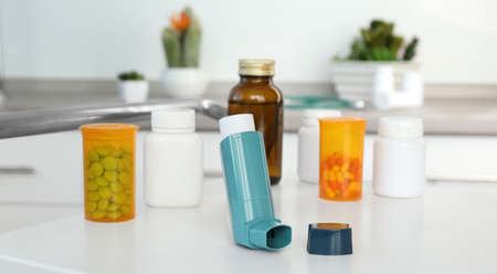 Asthma inhaler and medications on table