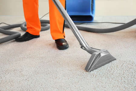 Dry cleaners employee removing dirt from carpet in flat