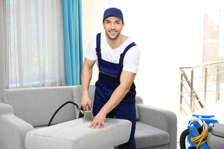 Dry cleaners employee removing dirt from furniture in flat