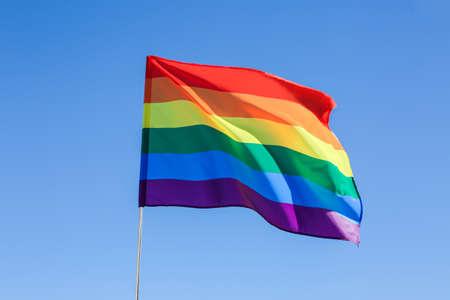 Gay flag on blue sky background