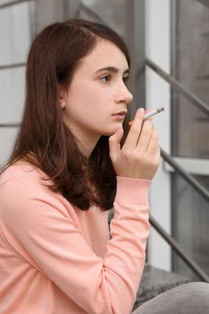 Teenage girl sitting on stairs and smoking