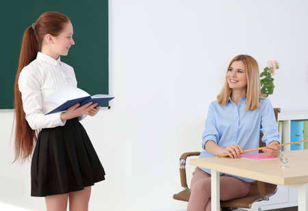Schoolgirl answering at blackboard in classroom