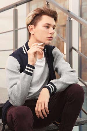 Teenage boy sitting on stairs and smoking