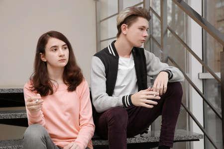Couple d'adolescents assis dans les escaliers et fumer