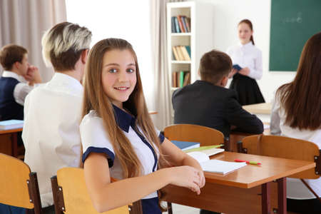 Cute schoolgirl at lesson in classroom