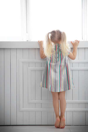 Cute little girl standing near window at home