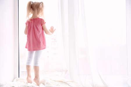 Cute little girl standing on windowsill