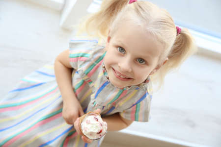 Cute little girl sitting on windowsill and eating ice cream Stock Photo