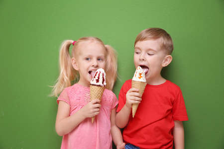 Cute little children eating ice cream on color background