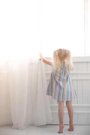 Cute little girl standing near window at home