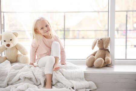 Cute little girl sitting on windowsill
