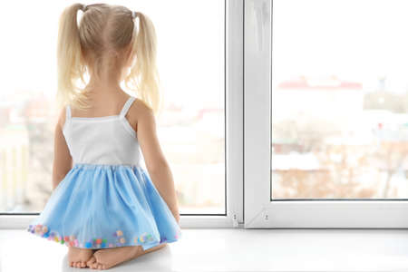 Cute little girl sitting on windowsill