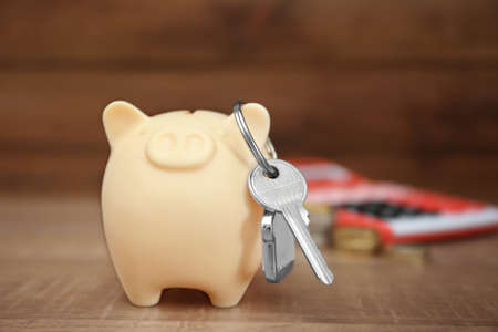 Savings concept. Piggy bank with key on wooden table Stock Photo