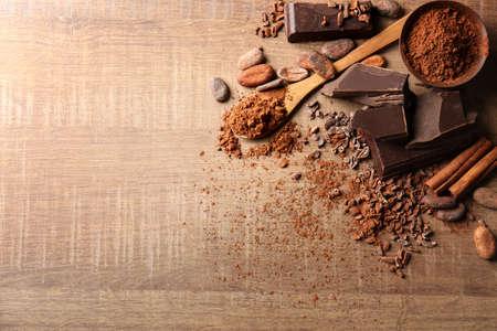 Zusammensetzung mit Kakaopulver und Stücken Schokolade auf hölzernem Hintergrund Standard-Bild