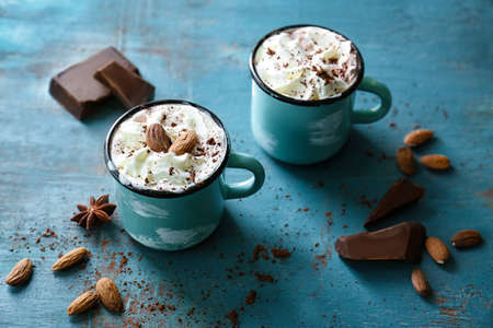 Cups of hot cocoa drink on wooden table