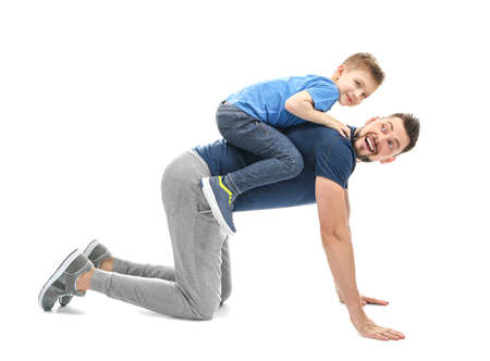 Handsome man playing with his son on white background