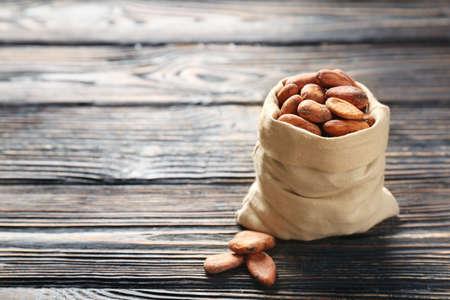 Sac de jute avec des fèves de cacao aromatiques sur une table en bois% 00 Banque d'images