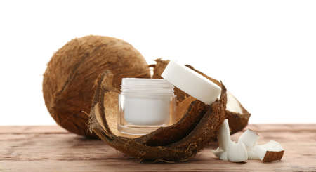 Jar with cream in coconut rind on wooden table