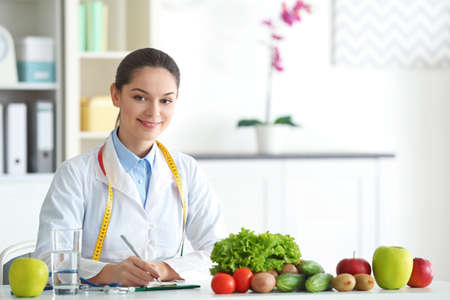 Young female nutritionist sitting at table with fresh vegetables and fruits in her office