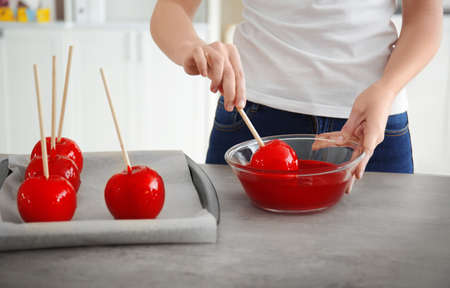 Woman dipping candy apple into glass bowl with caramel