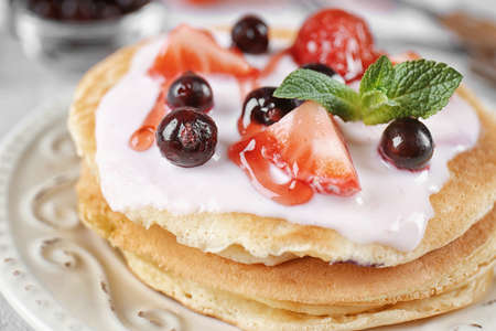 Delicious pancakes with berries and yogurt on plate