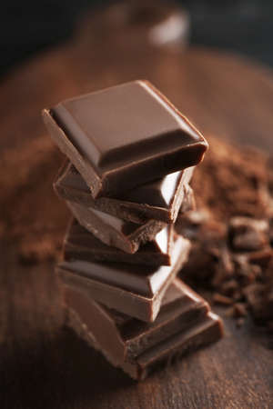 Stack of chocolate pieces on table, closeup
