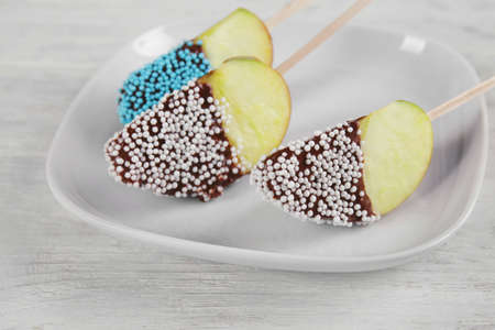 Plate with candied apple wedges on sticks Stock Photo