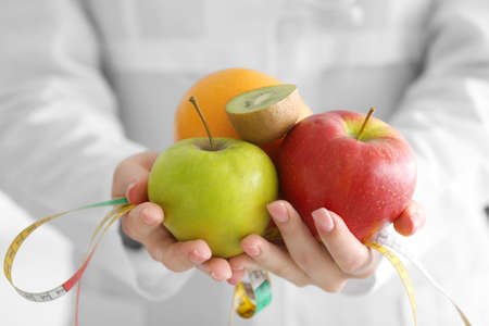 Young female nutritionist holding fresh fruits and measuring tape, close up