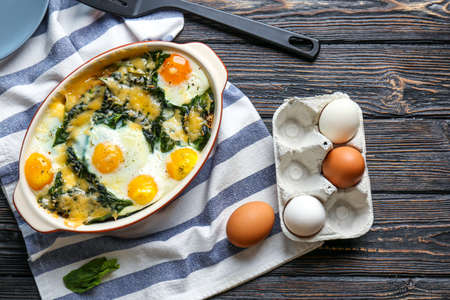 Baking dish with delicious cooked eggs Florentine and napkin on wooden background
