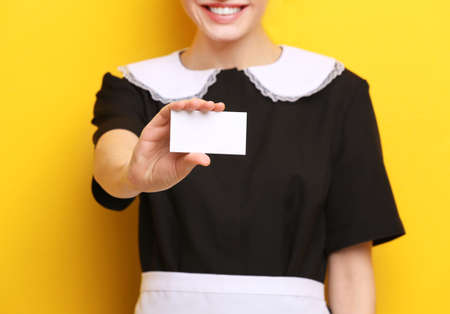 Young chambermaid with business card on color background, closeup