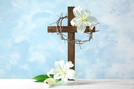 Composition with crown of thorns, cross and lily on light background Stock Photo