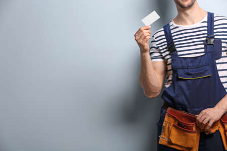 Handsome worker with business card on light background