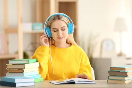 Jonge vrouwenzitting bij lijst en het luisteren aan audioboek