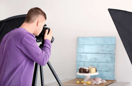 Young man photographing food in professional photo studio