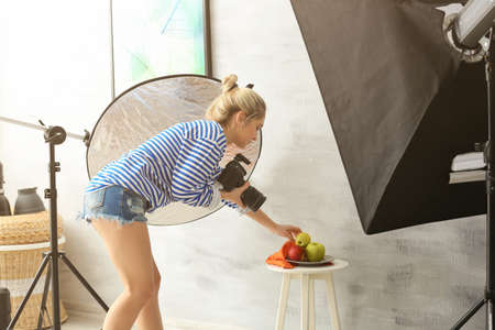 Young woman photographing food in professional photo studio