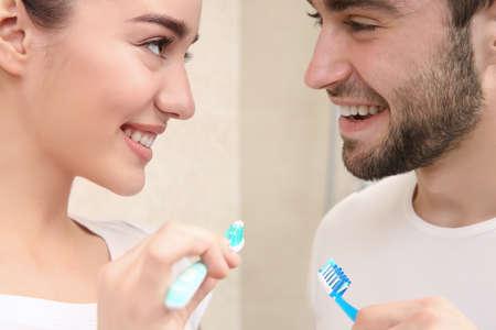 Young happy couple brushing teeth in bathroom Stock Photo