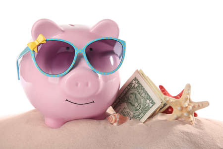 Vacation budget concept. Piggy bank with money and seashells on sand against white background Stock Photo