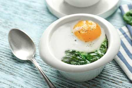 Bowl with tasty egg and spinach on wooden table Stock Photo
