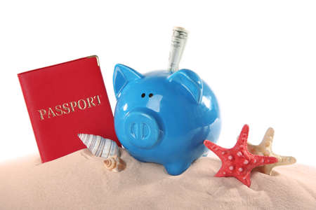 Vacation budget concept. Piggy bank with passport and seashells on sand against white background
