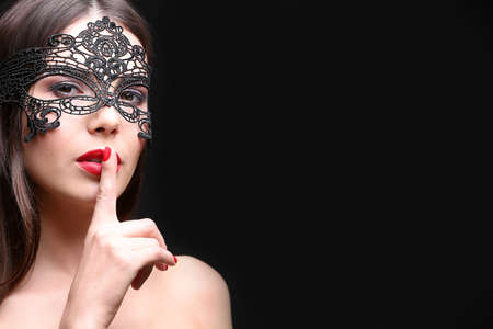 Beautiful young woman in mask on black background