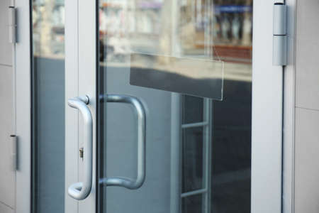 White glass door with sign on it, closeup Stockfoto