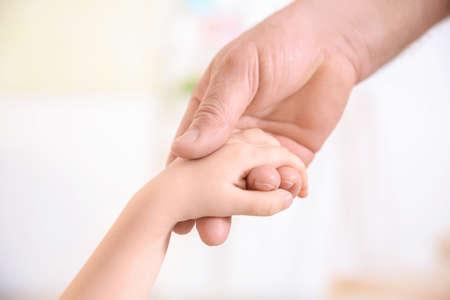 Senior man and little child holding hands, closeup